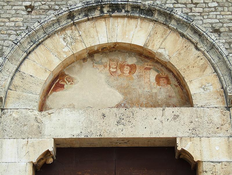 22 - Sermoneta, Abbazia di Valvisciolo: Lunetta del portale d'ingresso con affresco della Madonna in trono e Gesù Bambino tra i santi Pietro e Stefano, sec. XIII.